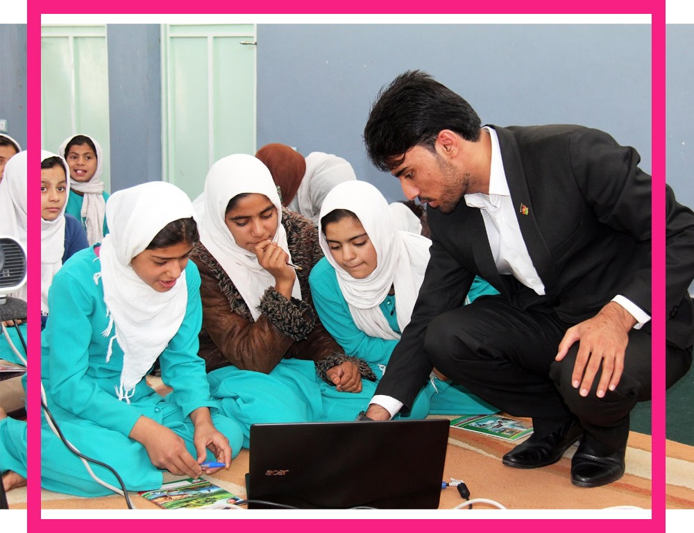 Teacher points at a computer while female students look at the screen
