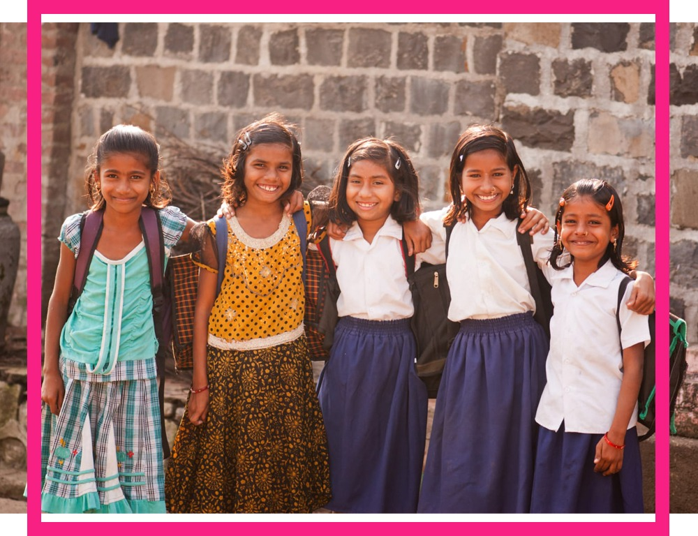 Group of school girls smiling at the camera on a sunny day