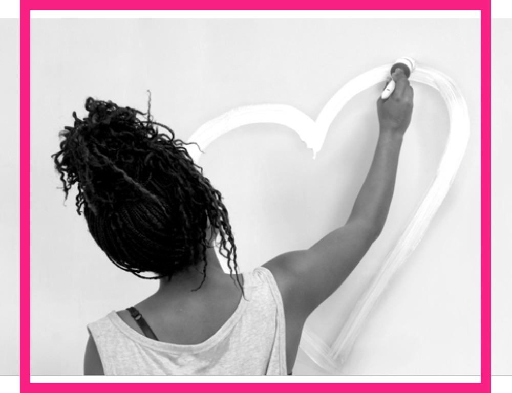 Black and white image of a young woman drawing a heart on a wall