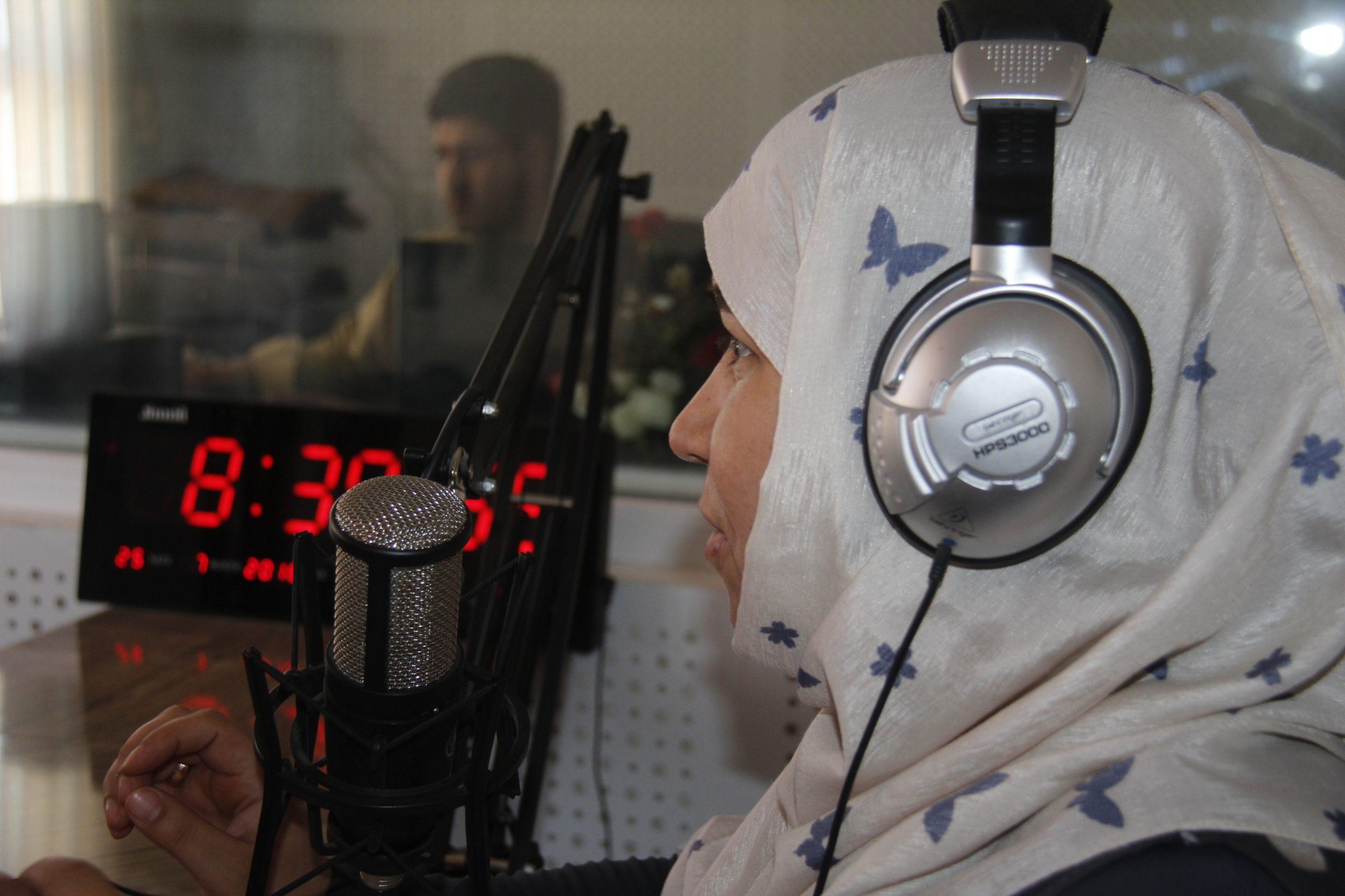 Afghan woman recording a radio program. She's wearing headphones