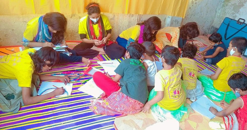 Children sitting on the floor and drawing at Hazeera's home