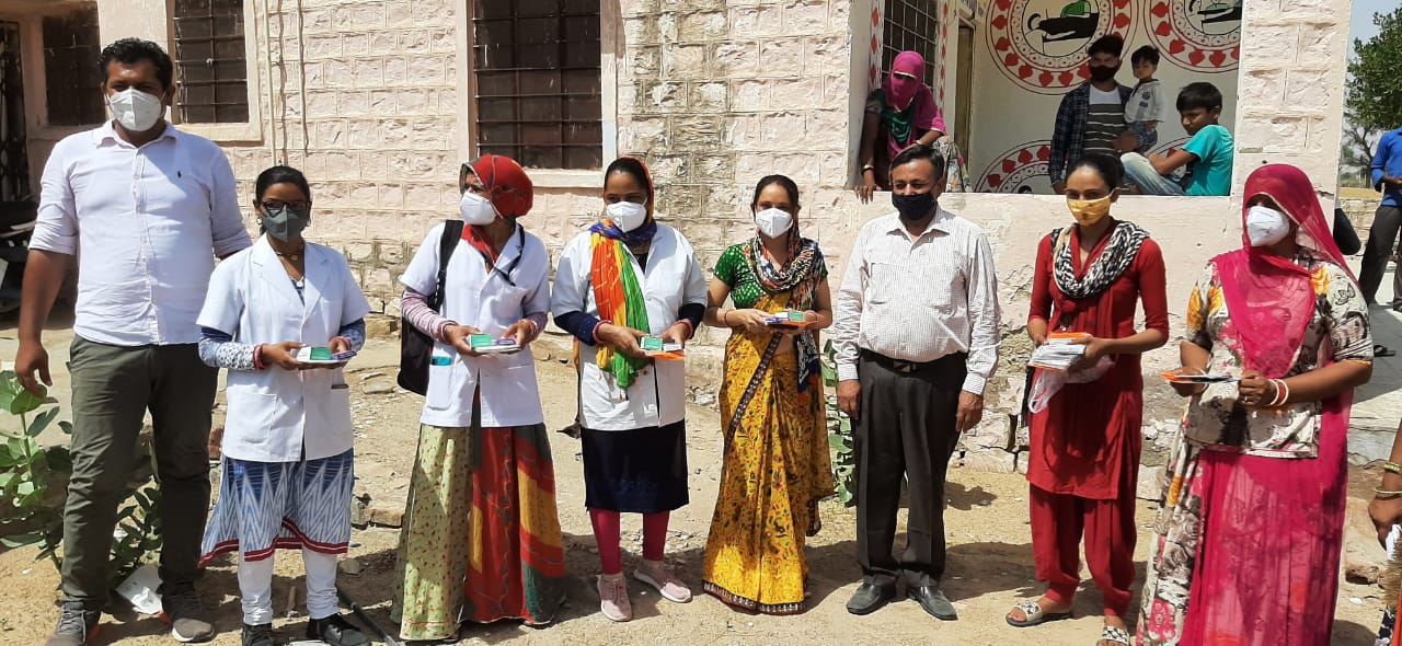 Group of doctors and medical staff posing in front of hospital in India, showing COVID 19 vaccines